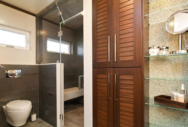 Стеклянные полки в ванной с темной отделкой